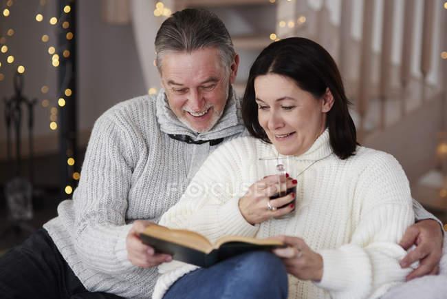 Glückliches älteres Paar liest ein Buch im Wohnzimmer — Stockfoto