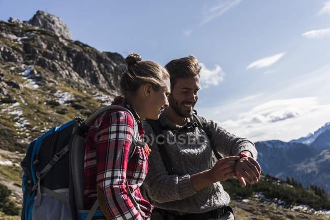Австрія, Тіроль, посміхаючись молода пара дивлячись на годинник в гірських пейзаж — стокове фото