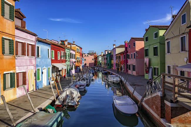 Italia, Véneto, Burano, canal con barcos y casas de colores - foto de stock