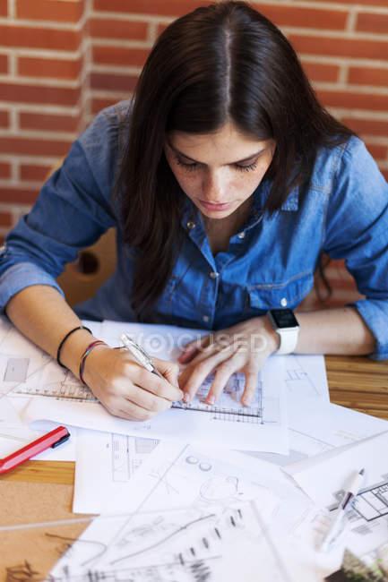 Mujer joven trabajando en la oficina de arquitectura, dibujando planos - foto de stock