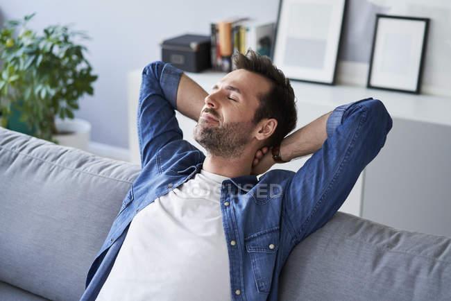 Sorridente uomo rilassato seduto sul divano e sognare — Foto stock