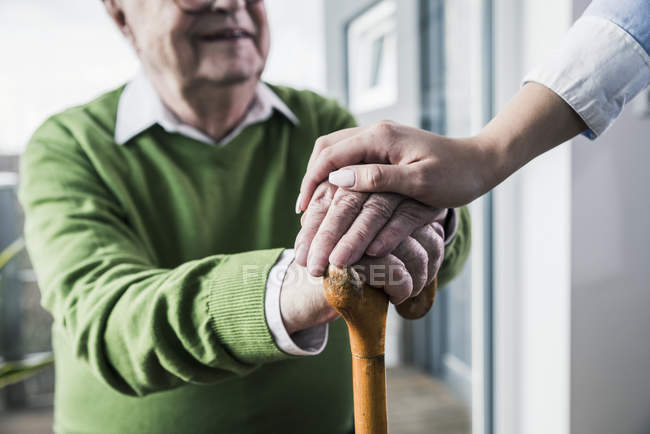 Close-up of woman holding senior man's hand leaning on cane — Stock Photo