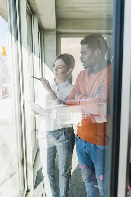 Mujer de negocios casual y hombre de negocios discutiendo el papel en la ventana — Stock Photo