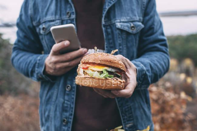 Hombre con hamburguesa y smartphone - foto de stock