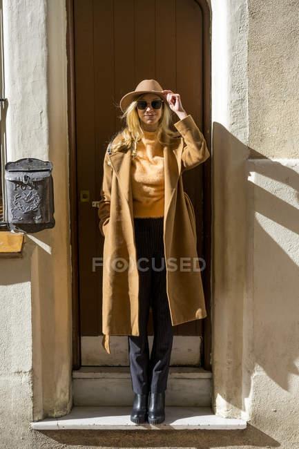 Retrato de mulher jovem na moda na entrada de casa — Fotografia de Stock