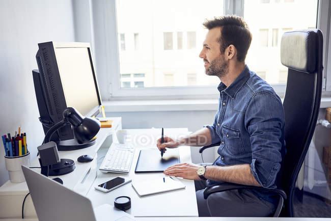 Designer grafico sorridente che lavora al computer alla scrivania in ufficio — Foto stock