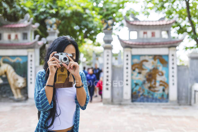 Vietnam, Hanoi, young woman taking a picture with old-fashioned camera — Stock Photo