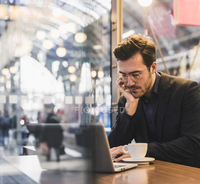 Молодий бізнесмен у кафе на вокзалі з чашкою кави і ноутбуком. — стокове фото