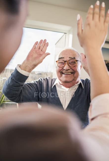 Glücklicher älterer Mann mit erhobenen Händen blickt junge Frau an — Stockfoto