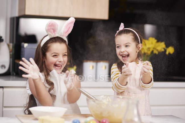 Duas irmãs divertidas se divertindo e cozinhando biscoitos de Páscoa na cozinha juntas — Fotografia de Stock