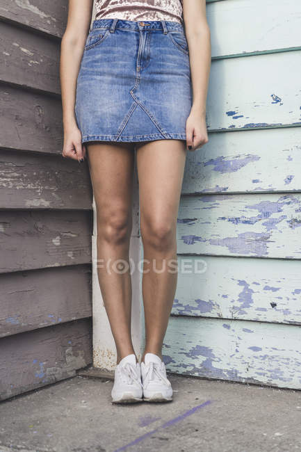 Cropped image of woman standing in corner in denim skirt — Stock Photo