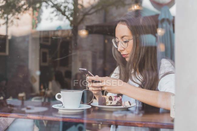 Donna con torta che controlla il suo cellulare in un bar — Foto stock