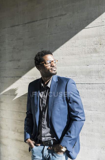 Бізнесмен стояв на сонці в бетонній стіні і дивиться — стокове фото