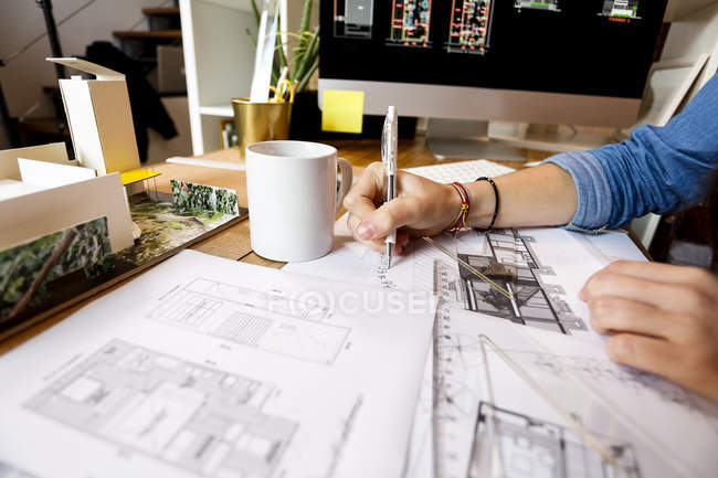 Young woman working in architecture office, drawing blueprints — Stock Photo