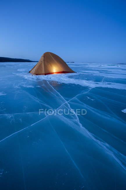 Russia, Amur Oblast, illuminated tent on frozen Zeya River at blue hour — Stock Photo