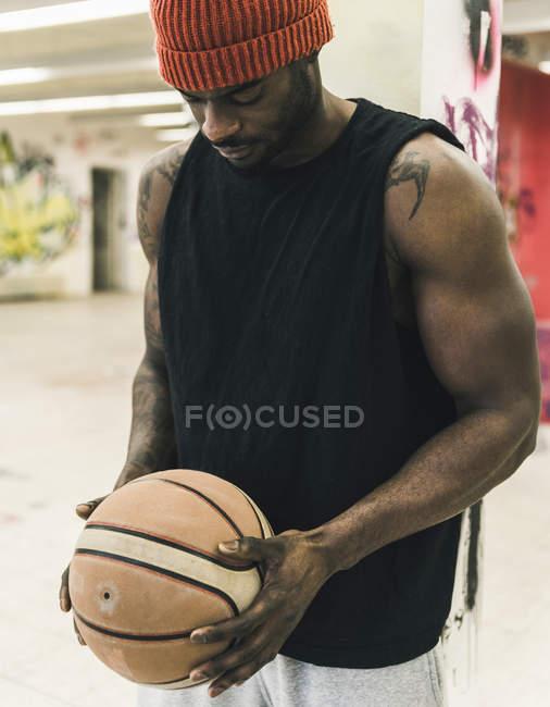 Африканский американец с татуировками и шерстяной шляпой, держащий баскетбольный мяч — стоковое фото
