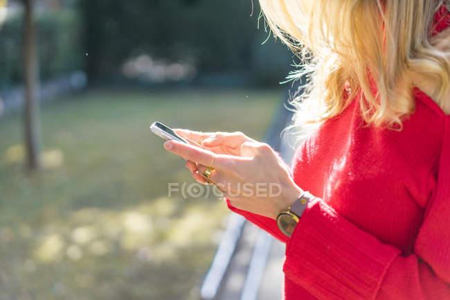 Крупный план женщины, использующей смартфон в саду — стоковое фото