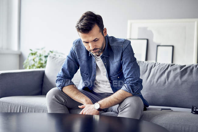 Worried sad man sitting on sofa — Stock Photo