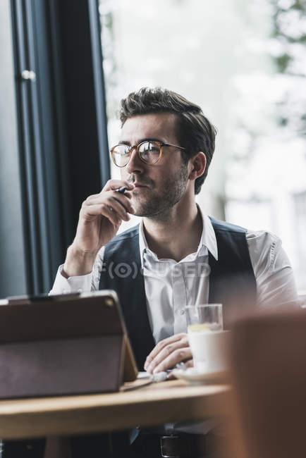 Молодий чоловік, який працює в кафе, користуючись планшетом і нотатками. — стокове фото