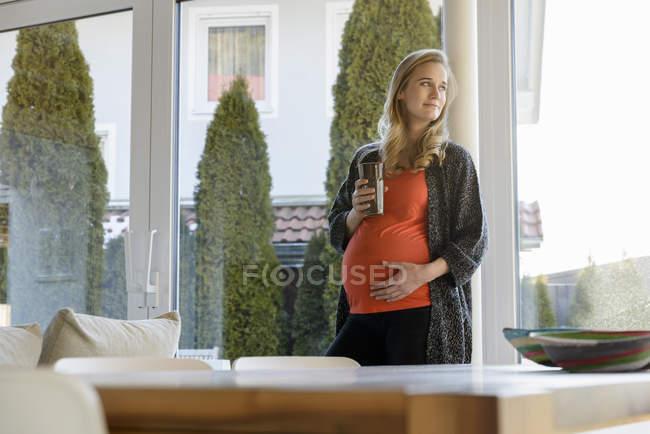 Улыбающаяся беременная женщина держит стекло и стоит у окна дома — стоковое фото