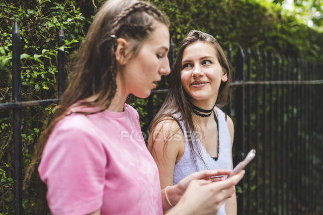 Two teenage girls with cell phone outdoors — Stock Photo