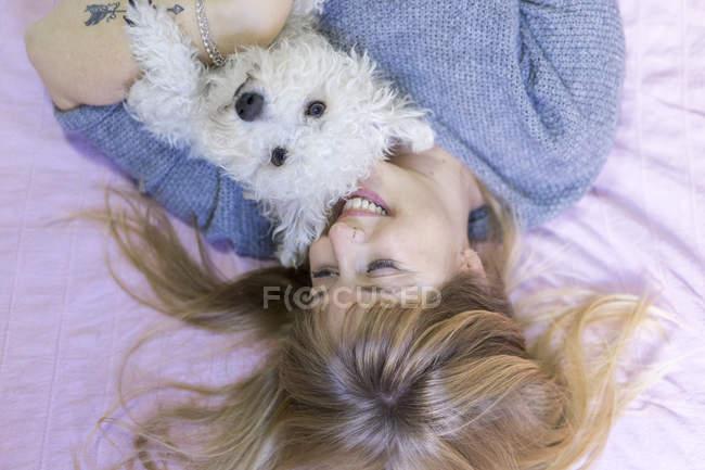 Mulher feliz que encontra-se na cama com seu cão — Fotografia de Stock