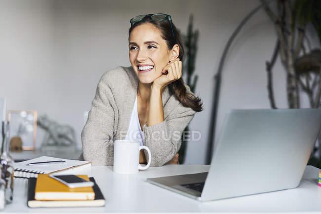 Счастливая молодая женщина дома с ноутбуком на столе — стоковое фото