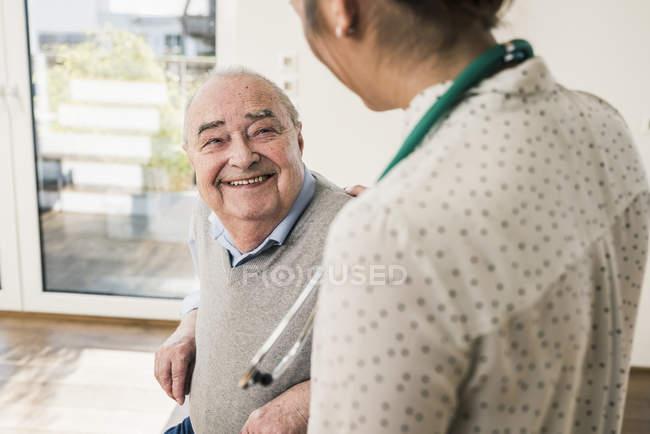 Senior man smiling at nurse at home — Stock Photo