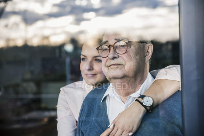 Portrait of young woman embracing senior man at the window — Stock Photo