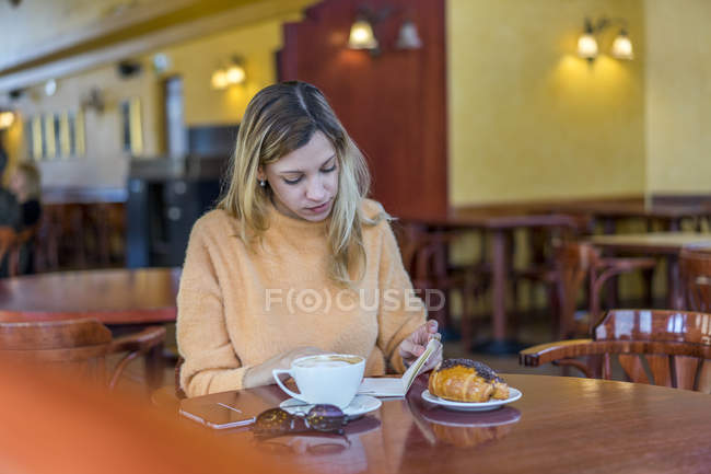 Young woman in a cafe with notebook, pastry and coffee — Stock Photo