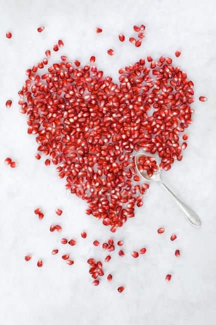 Насіння червоного граната поміщені у форму серця на білій поверхні — стокове фото