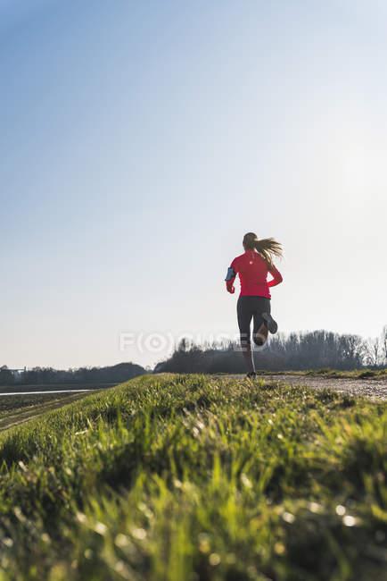 Giovane donna che corre sul sentiero rurale — Foto stock