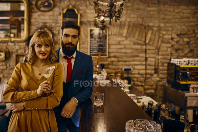 Portrait of elegant couple with drinks in a bar — Stock Photo
