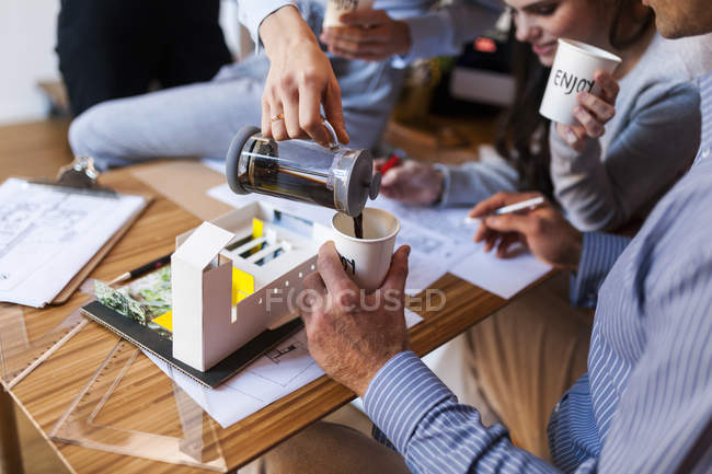 Team of architects working on a project, drinking coffee — Stock Photo