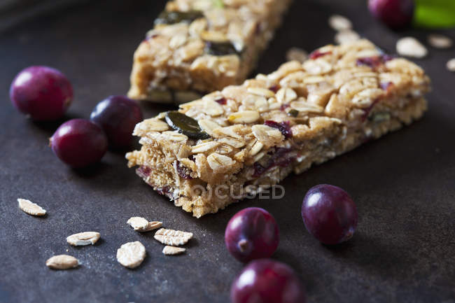 Muesli bars with cranberries and oat flakes on dark background — Stock Photo