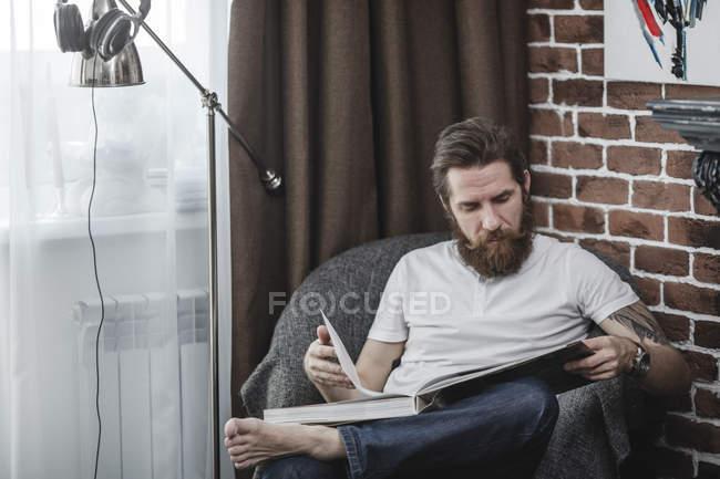 Людина сидить на кріслі і дивиться на каву-Табличні книги — стокове фото