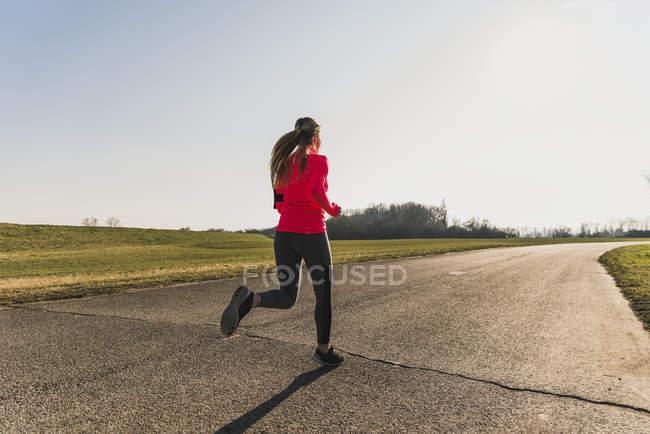 Молодая женщина бежит по проселочной дороге — стоковое фото