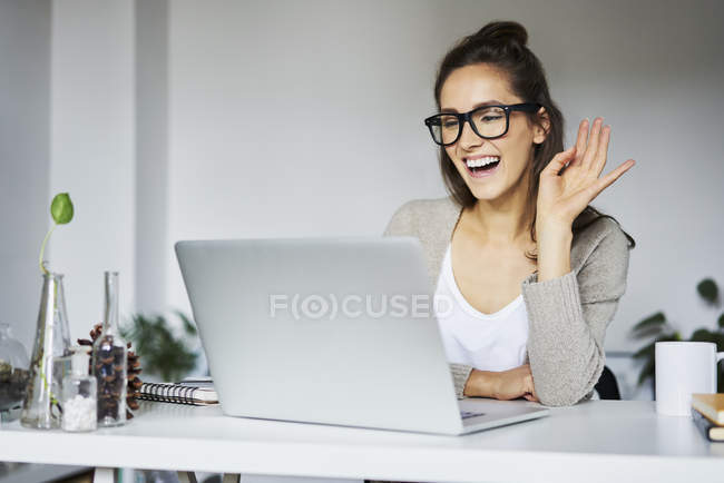 Young woman laughing during video chat at desk — Stock Photo