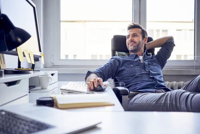 Relaxado homem sentado na mesa no escritório e olhando para a tela do computador — Fotografia de Stock