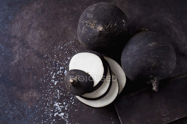 Sliced and whole black radishes on dark grunge background with rusty knife — Stock Photo