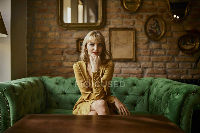 Portrait of elegant woman sitting on a couch — Stock Photo