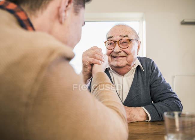 Lutte de bras d'homme aîné de sourire avec le jeune homme — Photo de stock