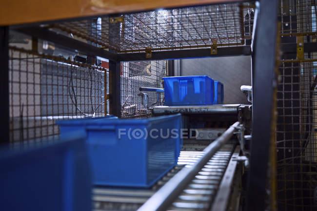 Синие коробки на конвейерной ленте — стоковое фото