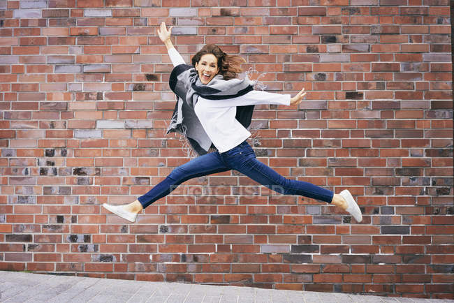 Happy young woman jumping in the air in front of brick wall — Stock Photo