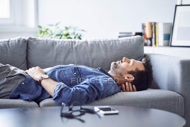 Relaxed man sleeping on sofa — стокове фото