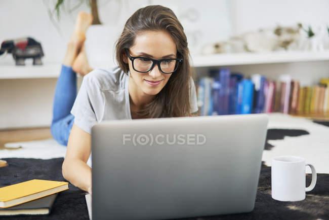 Jovem em casa deitada no chão e usando laptop — Fotografia de Stock
