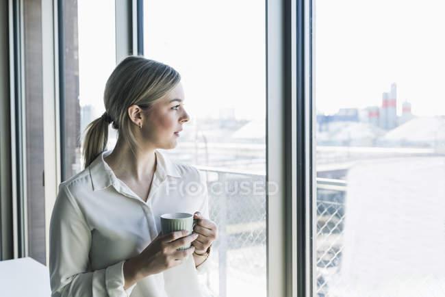 Молодая деловая женщина, выглядывающая в окно — стоковое фото