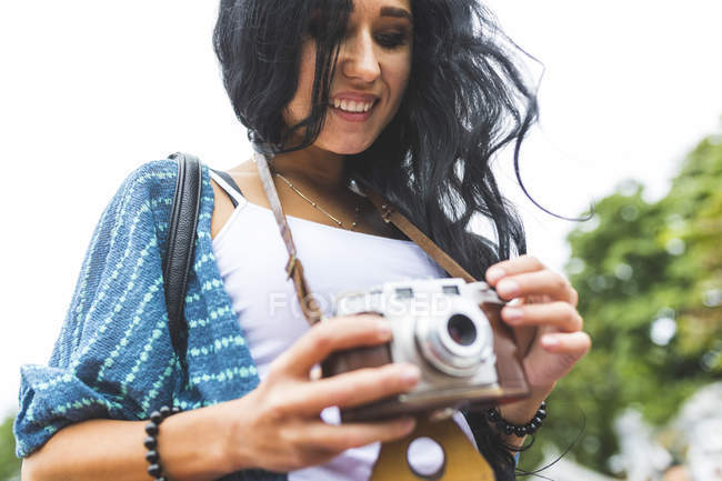 Smiling young woman with an old-fashioned camera — Stock Photo