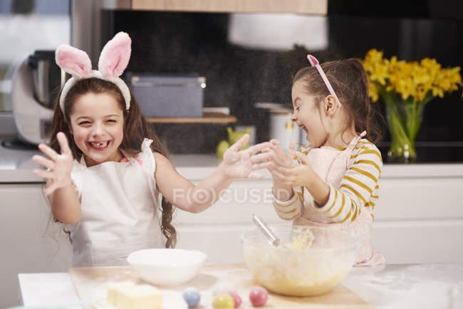 Две игривые сестры весело пекут пасхальное печенье на кухне вместе — стоковое фото