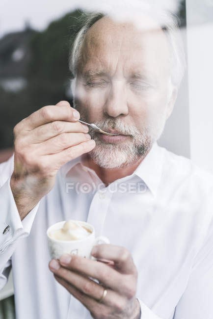 Portrait of mature man behind glass pane enjoying crema — Stock Photo